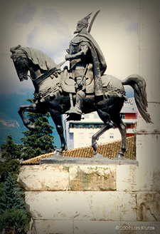 "Statue of Albania's national hero Gjergj Kastriot Skenderbeu or Skanderbeg who led the resistance against the Ottoman Turks in the 15th century. The sculpture was casted in 1968 to commemorate the 500th anniversary of his death. This monument sits in Tirana's main square, Skanderbeg square, and is flanked by the national flag of the double-headed eagle. This emblem, which also adorns Skanderbeg's chest armor, is believed to have been his coat of arms and was originally inspired by the Byzantine war flag. Not surprisingly, Albanians refer to their country as Shqipëria (pronounced schip-ree-ya) meaning ""Land of Eagles."""