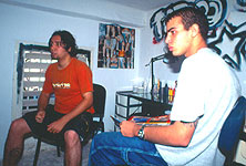 Mikail (in orange Adidas shirt) explaining life and work in Havana. © 2003 Lars Krutak.
