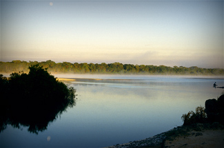 A lone Kayabi fisherman (far right) casts his line into the Xingu River at dawn. His fishing platform is a submerged dugout canoe.