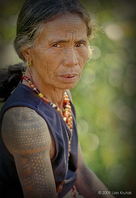 Elisa and Lukya of Buscalan wear various patterns of snake scales and /\/\/\/\ motifs representing stairs or steps. Tattooed scales are derived from the python. 80 year-old Lukya with white tank-top and numerous beads said Whang-Od made all of her marks in three days when she was about thirteen years old.