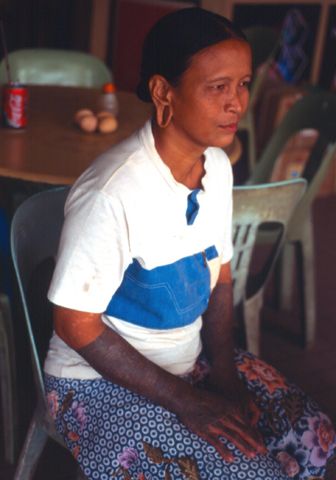 Sihan woman with arm tattoos. Her forearms are tattooed with hornbill (tingang) and kalong kelunan motifs, while the wrists are marked with 'shoots of bamboo' (fertility symbols). Kalong kelunan, a stylized human figure in a squatting position seen between the S-fret designs, has various forms and usually is reinforced by a stylized hornbill motif (at top): at other times it is anchored by aso' or the dragon-dog design. Aristocratic women wore the kalong, because it was believed that they were closer to the spirit world than laypersons and only they could resist any negative magic associated with the design. In the distant past, the motif may have represented a ritual offering, depicting a slave sacrifice, or a guardian spirit.